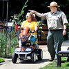 John P. Cleary |  The Herald Bulletin<br /> Kelley Morgan, Mounds State Park Interpretive Naturalist, points out things to Kim Ousley who's riding the new scooter the park has that the Friends of Mounds Park had donated to the park for people with disabilities to get around the park easier.
