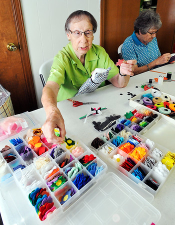 John P. Cleary |  The Herald Bulletin<br /> Berine Lewis reaches to get cutout pieces to decorate the Love Bear she is working on.