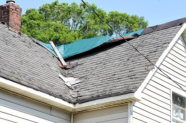 John P. Cleary |  The Herald Bulletin<br /> Tarps cover up holes in the roof of Beverly Master's house on Church Street in Alexandria where she as apparently been scammed out of money and roofing materials by a contractor hired to fix the roof.