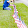 "Don Knight | The Herald Bulletin<br /> Charlie Carter, brother of Battery Experts owner Joe Carter, lines Broadway with flags for the Fourth of July holiday on Friday. Several northside businesses line their property with flags for the holiday. ""It's just real nice to have the northside decorated like this,"" Charlie Carter said. The North Anderson Business Association started the tradition and Northgate True Value hardware sells the flags at cost to business displaying them."