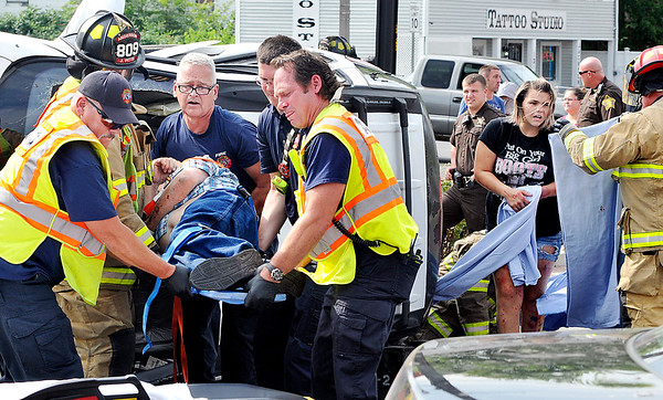 John P. Cleary    The Herald Bulletin<br /> Anderson Fire Department personnel lift this man out of a mini-van thats on it's side as a female gets aid from a firefighter after crawling out of the back of the van after being involved in a multi-car crash at 14th and Jackson Street's Wednesday afternoon.