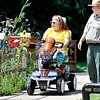 John P. Cleary |  The Herald Bulletin<br /> Kim Ousley tries out the new scooter at Mounds State Park with Kelley Morgan, park Interpretive Naturalist, as they observe the butterfly garden<br /> together.