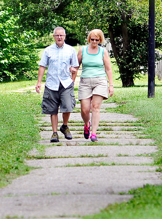 John P. Cleary |  The Herald Bulletin<br /> These folks walk along a section of trail at Shadyside Park Monday that has the grass growing through the cracks of the pathway. The City of Anderson will spend an estimated $200,000 to resurface the 2.5-mile trail system around the lake at Shadyside Park starting next week.<br />  <br /> <br /> <br /> Walkers using the trails say the resurfacing has been needed for quite awhile.