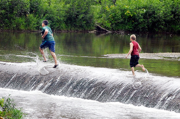 John P. Cleary |  The Herald Bulletin<br /> On a hot, humid day these kids have fun splashing around along the spillway at the Killbuck Wetlands Thursday afternoon.
