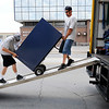 Don Knight | The Herald Bulletin<br /> From left, Bryce Triche and Steven Pence with Two Guys & a Truck move a filing cabinet into the Madison County Council of Governments new offices in the Star Bank building on Thursday.