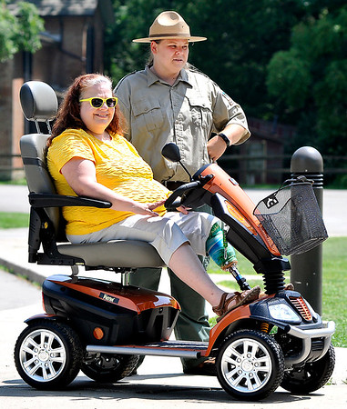 John P. Cleary |  The Herald Bulletin<br /> Kim Ousley tries out the new scooter at Mounds State Park with Kelley Morgan, park Interpretive Naturalist. Friends of Mounds Park had a scooter donated to the park for people with disabilities to get around the park easier.