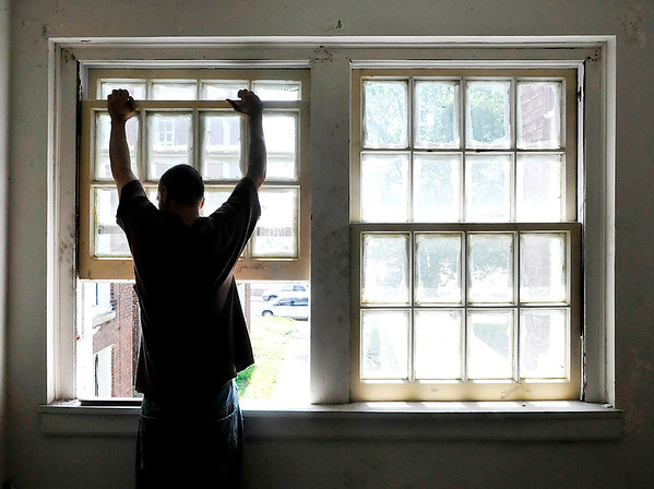 John P. Cleary |  The Herald Bulletin<br /> A worker checks the windows in this apartment as the Downtown Historical and Cultural Commission won't allow vinyl replacement windows to be used in the historic structure. They are having to repair the existing windows, or replace as close to original as possible, to maintain the historical integrity of the building.