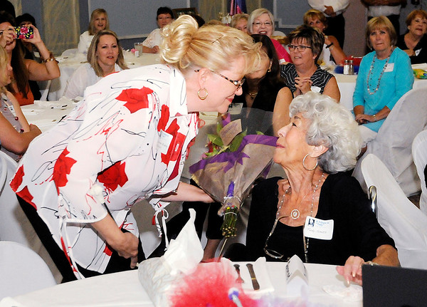 Don Knight | The Herald Bulletin<br /> Dorinda Harnish gives Tudy Smith a bouquet of flowers during the Elwood Twirlers reunion to recognize Smith at the Elwood Opera House on Saturday.