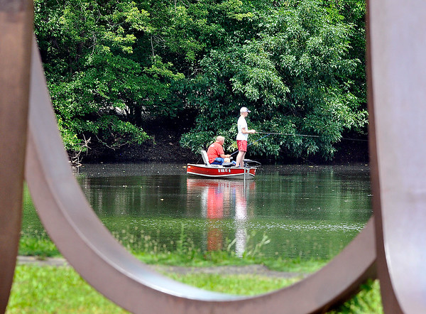 John P. Cleary    The Herald Bulletin<br /> These anglers are framed inside the curves of the Changing Forms steel sculpture as they fish the lake at Shadyside Park Monday.