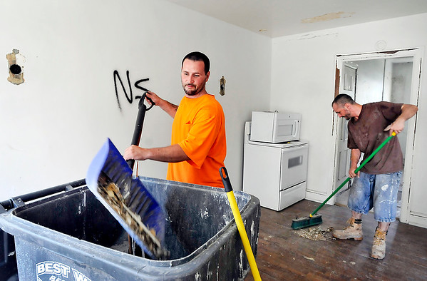 John P. Cleary |  The Herald Bulletin<br /> Mathew Morgan and James Weidemann clean out the debris in one of the apartments as work continues on rehabbing the Delaware Court Apartments by a Fort Wayne investment company.