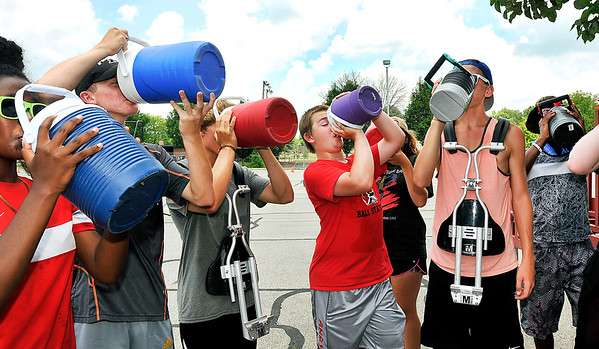 John P. Cleary |  The Herald Bulletin<br /> These members of the Anderson High School Marching Highlanders drum line chug down their water as they take a break from practice on a hot, humid Tuesday afternoon. As the band works toward the State Fair Band Contest in several weeks they placed third this past weekend at the Centerville High School Band Contest.