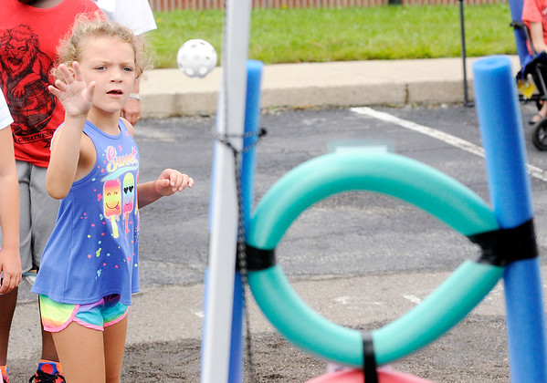 Don Knight   The Herald Bulletin<br /> Abygail VanBuskirk, 6, tosses a ball through a hoop while playing a game during Harrison College's Back to School Carnival on Friday. The event included games, face painting, an inflatable and giveaways.
