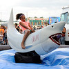 "Don Knight | The Herald Bulletin<br /> Kyla Newpert, 9, rides a mechanical shark during ""Fire it Up on the Fourth"" at Hoosier Park on Tuesday."