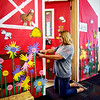 John P. Cleary |  The Herald Bulletin<br /> Alexandria-Monroe Elementary School 2nd grade teacher Monica Etchison puts the finishing touches on the entrance to her room Friday afternoon in the form of a barn along with flowers made up of the hand prints of students. Classes start Monday for the students.