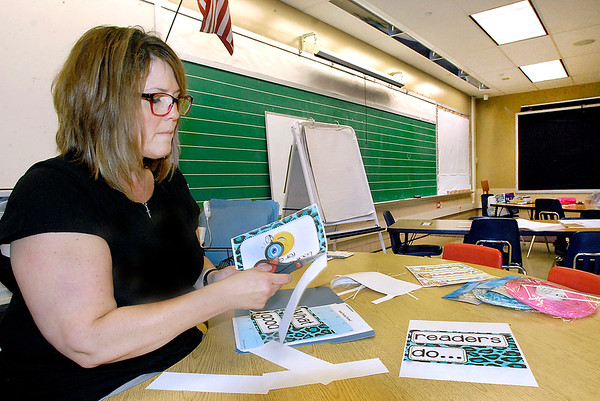 John P. Cleary    The Herald Bulletin<br /> First-year teacher Shelly Bruzzese cuts out material as she works Friday preparing her kindergarten classroom at Alexandria-Monroe Elementary School for the first day of school Monday.