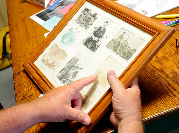 Don Knight   The Herald Bulletin<br /> Vaughn Bracken points to pictures of his father Carl Bracken farming as he talks about changes in technology in agriculture at Bracken Farms on Wednesday.