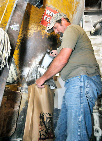 John P. Cleary    The Herald Bulletin<br /> Greg Gist fills bags of cracked corn in the feed mill.