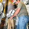 John P. Cleary |  The Herald Bulletin<br /> Greg Gist fills bags of cracked corn in the feed mill.