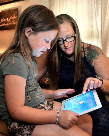 John P. Cleary |  The Herald Bulletin<br /> Kira Smith works with her daughter Katy Porter, 6, as she uses an iPad.