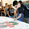 Don Knight | The Herald Bulletin<br /> James Weaver, 14, signs a banner for students in the Class of 2021 at Anderson High School on Thursday. The school held their freshman orientation for parents and students Thursday. The banner will hang in the school for the students high school career as a reminder of their commitment to graduate. Students return to the classroom on August 2nd.