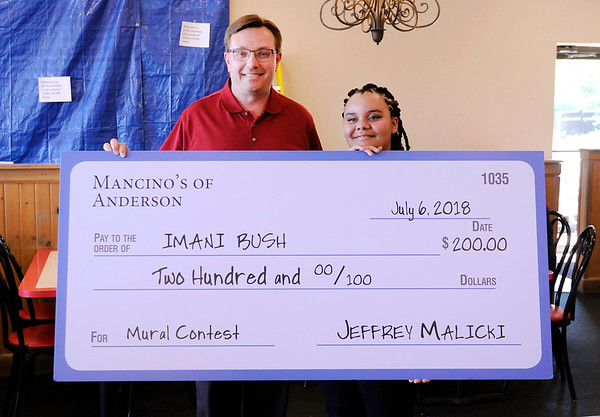 Don Knight | The Herald Bulletin<br /> Mancino's owner Jeff Malicki awarded Anderson High School student Imani Bush $200 for her winning mural design.