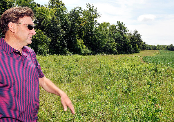 John P. Cleary | The Herald Bulletin<br /> John Simmermon looks over the area next to his bean field where he has planted grasses as a conservation effort for a voluntary program by the U.S. Department of Agriculture to keep acreage along White River natural and to help keep the river clean. The river is just on the other side of the tree line in the background.