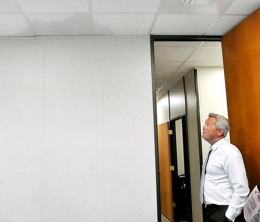 John P. Cleary | The Herald Bulletin<br /> Madison County prosecutor Rodney Cummings looks at the ceiling in his office Wednesday where a water leak from the fourth floor soaked ceiling tiles and ran down the walls in several third floor offices in the prosecutor's office. The leak was caused by a clog in a water pipe in the just remodeled upper floors of the Government Center.