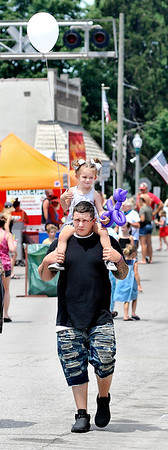 John P. Cleary | The Herald Bulletin<br /> With her balloons in tow, Ariyah Foust, 3, gets a better view of the Lapel Village Fair from the shoulders of her step-dad, Justin Chesnut.