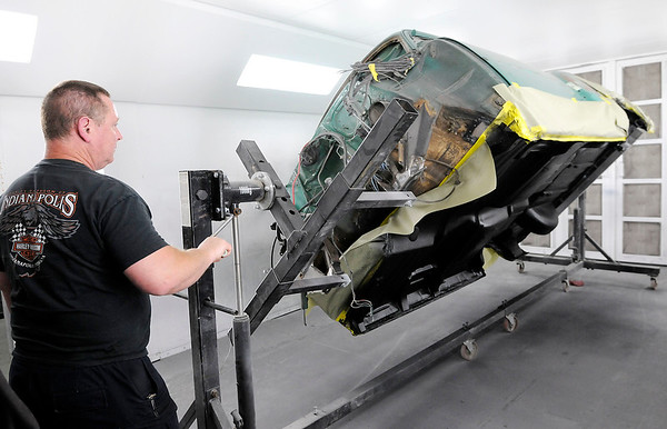 Don Knight | The Herald Bulletin<br /> American Classics Restoration owner Vladimir Kryjanovski rotates a car body on a rotisserie to get a look at the bed liner coating on the bottom. The bed liner provides protection and some sound deadening.