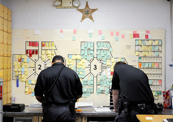 Don Knight | The Herald Bulletin<br /> Officers work in the book-in area of the jail. Each piece of paper on the board represents an inmate housed at the jail.