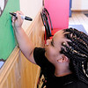 Don Knight | The Herald Bulletin<br /> Anderson High School student Imani Bush signs her mural at the Mancino's in Anderson after it was unveiled on Friday.