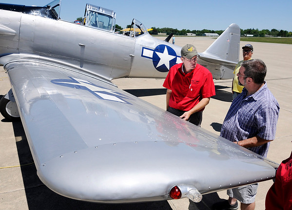 Don Knight | The Herald Bulletin<br /> John Shuttleworth, left, talks to Brett Johnson about the control surfaces of his T-6 Texan during Aviation Days at the Anderson Airport on Saturday.