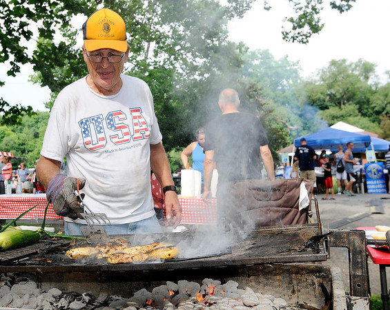 Don Knight   The Herald Bulletin<br /> Dick Creger grills chicken at the Pendleton Lions Club booth during Pendleton's 4th at the Falls celebration on Wednesday.