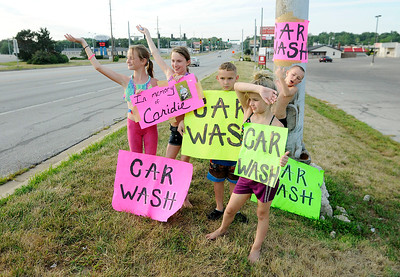 Don Knight | The Herald Bulletin From left, Kyndall Carmack, Katana Kirk, Aiden-Joe Hammers, Samirah Kirk and Blade Kirk wave to passing motorists during a car wash fundraiser.