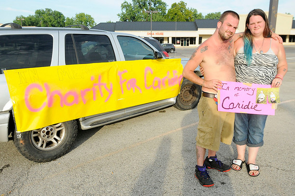 Don Knight | The Herald Bulletin<br /> Darrelwyn Rodney Wisler II and Nikki Wisler are sunburned after a day of washing cars trying to raise funds for their daughter Caridie's funeral.