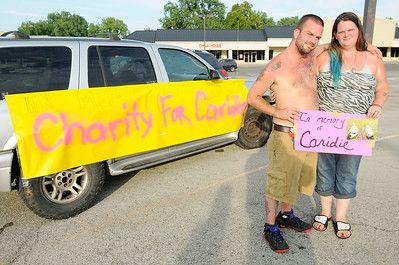 Don Knight | The Herald Bulletin Darrelwyn Rodney Wisler II and Nikki Wisler are sunburned after a day of washing cars trying to raise funds for their daughter Caridie's funeral.