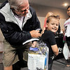 John P. Cleary | The Herald Bulletin<br /> Gordon Bright helps his grandson, Oliver Wise, 5, try on his new backpack full of school supplies at the Alexandria city-wide Back to School Rally Monday evening. Oliver will be starting pre-kindergarten on August sixth.