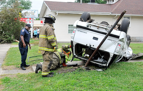 John P. Cleary   The Herald Bulletin<br /> Anderson police and fire personnel check this vehicle after the driver veered across Broadway, hit a tree and then flipped several times landing upside down the front yard of 1203 Broadway.