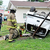 John P. Cleary | The Herald Bulletin<br /> Anderson police and fire personnel check this vehicle after the driver veered across Broadway, hit a tree and then flipped several times landing upside down the front yard of 1203 Broadway.