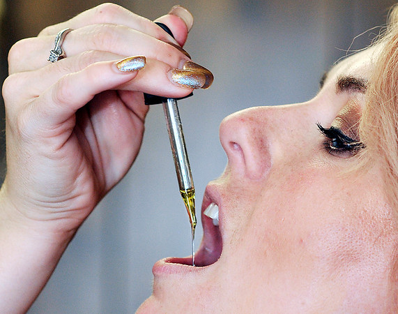 John P. Cleary | The Herald Bulletin <br /> Morgan Johns takes CBD oil and used to sell it at her shop, Rebellious Make Up by Morgan, in Elwood. Here Morgan takes her daily dose of the CBD oil.