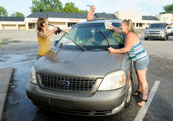 Don Knight | The Herald Bulletin<br /> From left, Lisa Ipock, Scotty Parker and Hollie Kirk dry a van during a car wash fundraiser on Thursday. The car wash was raising money for 5-year-old Caridie Wisler's family to cover her funeral expenses.
