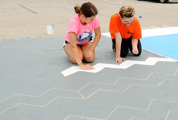 Don Knight | The Herald Bulletin<br /> Allyson Partlow, left, gets some help from Kylie Higgs laying out a chevron pattern to paint  on her parking spot on Tuesday. Senior's personalizing their parking spot has become a school tradition. Anderson students return to the classroom on Wednesday August 1st.