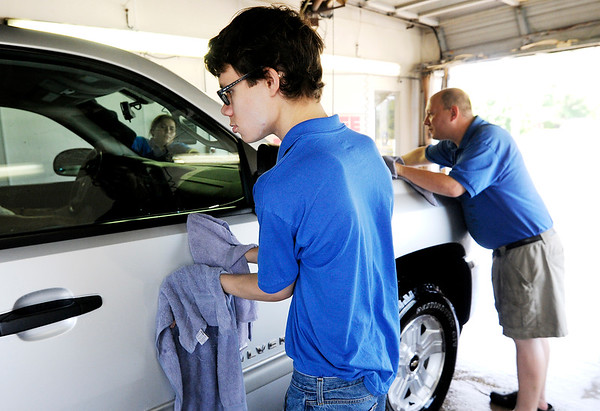 Don Knight | The Herald Bulletin<br /> Cody Bennett dries a truck as it exits Clancy's Car Wash. William Lantz from the Hopewell Center works with Bennett helping him integrate in a work environment.