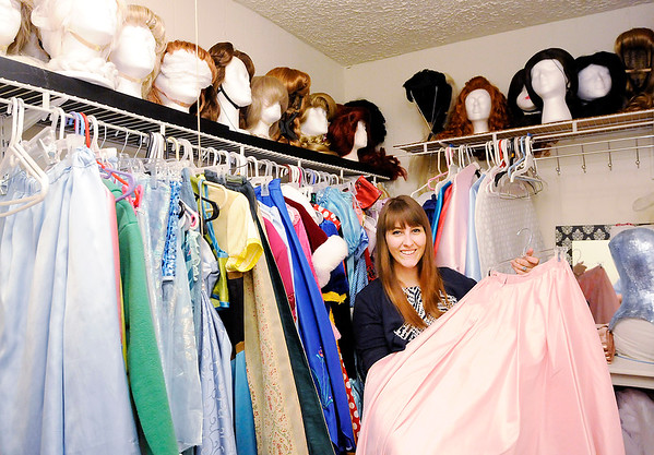 Don Knight | The Herald Bulletin<br /> Ashley Heiney holds up her Sleeping Beauty dress in the closet where she stores her collection. Heiney has turned her hobby of princess dresses into a business, Once Upon a Princess.