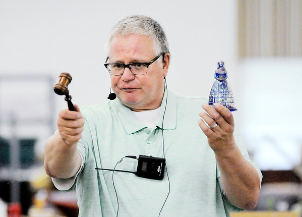 Don Knight | The Herald Bulletin<br /> Randy Holland, owner of Able Auction Service, takes bids for a glass bell during an auction at the Rangeline Community Center on Saturday.