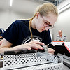 John P. Cleary | The Herald Bulletin<br /> First year science teacher at Wes Del High School, Jeri Smith, attaches one of the drive wheels to a motor as she puts together a VEX robot during robotics training at Purdue Polytechnic Tuesday.