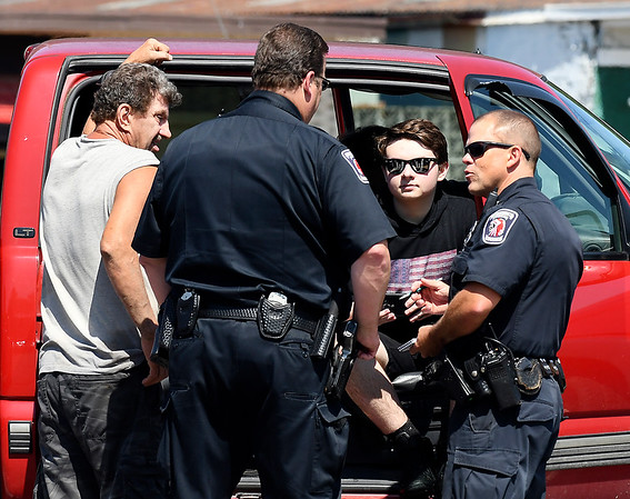 John P. Cleary | The Herald Bulletin<br /> A 15 year-old boy, third from left, was safe after he and his grandfather, left were kayaking on White River and the grandfather capsized near Derby Downs. Here they talk to APD officers after the boy escaped the swift current near Grandview Golf Course.