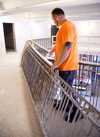 John P. Cleary | The Herald Bulletin<br /> Kameren Mathews, foreman for Maxwell Construction,  looks over a section of the old mezzanine railing that had to be taken out for new construction but said they have found a company that can recreate the design to replace it.