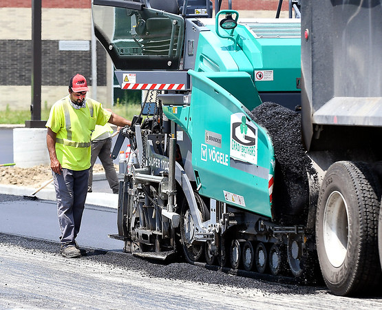 John P. Cleary | The Herald Bulletin<br /> Dave Radcliff, of Grady Brothers of Indianapolis, adjusts the paver as they lay down fresh asphalt on the lots and driveways around Anderson Intermediate School Thursday.