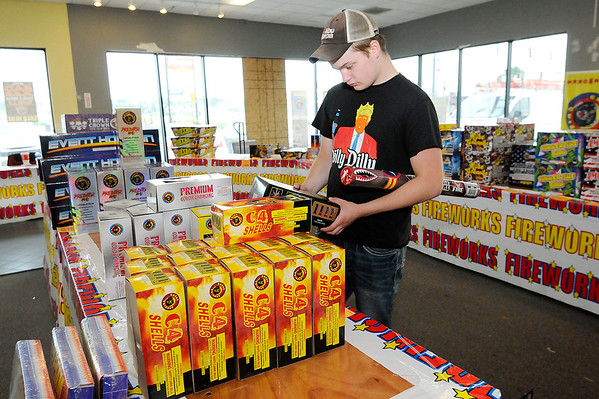 Don Knight | The Herald Bulletin<br /> Janson Fuller picks out fireworks at a pop-up store in the old Blockbuster at  18th Street and Scatterfield Road on Friday.